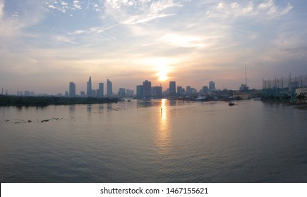 River city view landscape at twilight sunset. Boat on river with tranquil water. Hochiminh city Saigon vietnam cityscape building with Bitexco tower. Saigon river landmark view with cloud and sunlight
