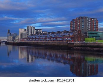 The River Clyde in Glasgow at night. Modern buildings between deep blue sky and river.