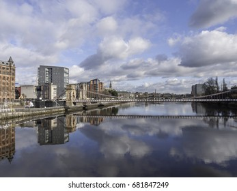The River Clyde in Glasgow, Scotland, Seen on a fine day with mirror-like reflections of the waterfront buildings in the still water.