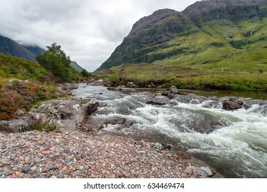 The river Coe flowing through the valley below mountains at Glencoe in the Scottish Highlands