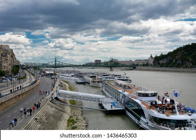 River Cruise boats on Danube River in Budapest - June, 2018 Row of cruise ships on shore. Moored Cruise Ships at Danube River Pontoons in Budapest, Hungary. Panoramic view of river shore