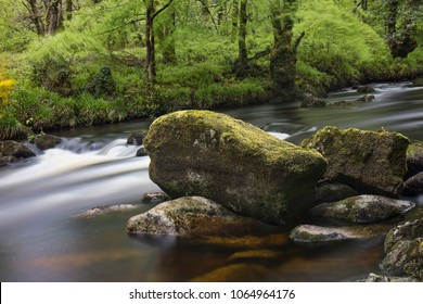 River Dart milky water with large rocks at Dartmeet in Dartmoor