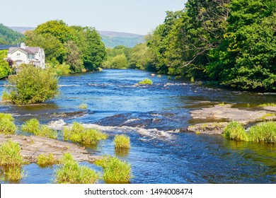 The River Dee flows fast between densley wooded banks on a bright summers day in Llangollen, Wales