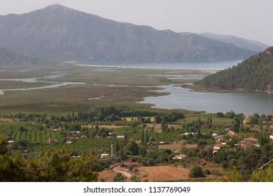 River delta effusing into the mediterranean sea and meandering through a rural valley