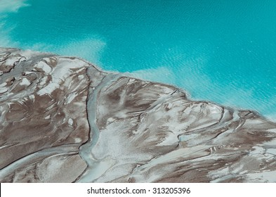 River delta flowing into the blue pond. Top view. Aerial photography.