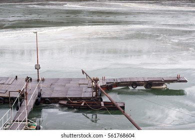 River dock and fishing boat on frozen river during cold winter day.