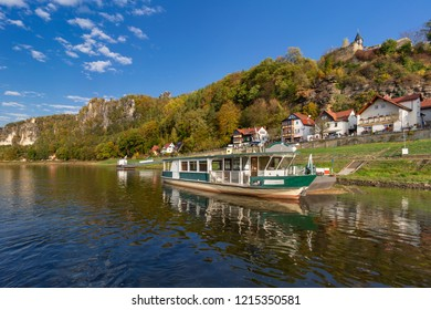 The river Elbe with ferry in the village Rathen in in the Saxon Switzerland National Park, Germany, (German: Nationalpark Sächsische Schweiz) in late summer / early autumn.