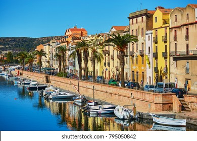 River embankment with typical colorful Italian houses on a street of Bosa, Sardinia, Italy