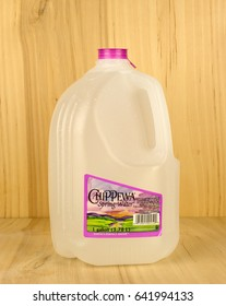 RIVER FALLS,WISCONSIN-MAY 17,2017: A gallon jug of Chippewa brand spring water with a wood background.