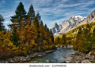 The river in Ferret Valley during the autumn season with the Mont Blanc wall in the background and clouds in the sky
