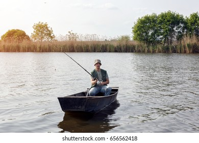 river fishing- man catching fish in boat