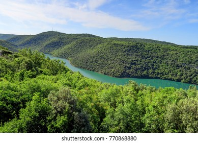 A river or fjord of turquoise water cuts through green hills north of Rovinj, near Pula, Croatia
