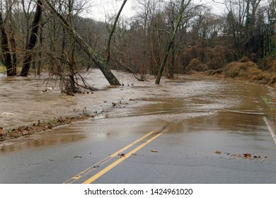 A river floods onto a road making it hazardous and impassable