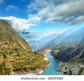 River flowing in a canyon backdrop of mountain ranges and cloudy sky in the Himalayas