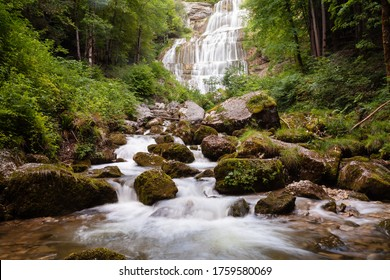 River flowing quickly in forest area, many mossy stones. Waterfall Cascade de l'Eventail in back. France, Europe.
