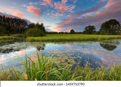 A river flowing through lush fresh green fields at sunset with a colorful sky - Meppel, Drenthe, The Netherlands