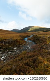 River flowing towards the valley at the Fairy Pools on Isle of Skye during a cloud-covered autumn day (Isle of Skye, Scotland, United Kingdom, Europe)