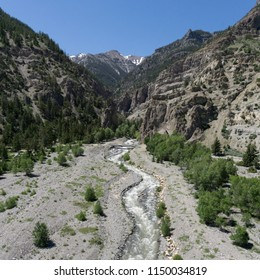 River flows down out of a Wyoming mountain valley bordered by green trees.