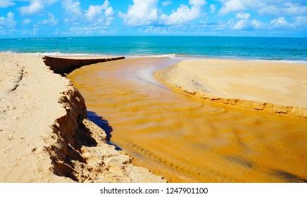 River flows into the sea at beautiful, sandy beach in Arraial d'Ajuda, near Porto Seguro, Bahia, Brazil