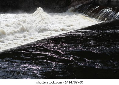 River flows out of a damn, creating strong splash.