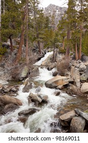 A river flows over some rocks and debris into Lake Tahoe in California.