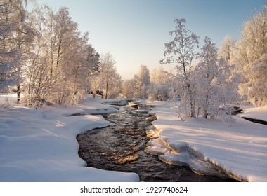 The river flows through the snowy rural landscape. Despite of the cold weather, the water has not been totally frozen.