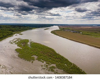River flows through the taiga. River landscape, beautiful sky reflection in water. Thunderstorm and rain weather. Vasyugan Swamp from aerial view. Tomsk region, Siberia, Russia