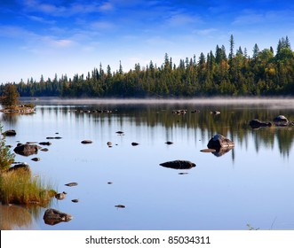 River in forest with stones and fog