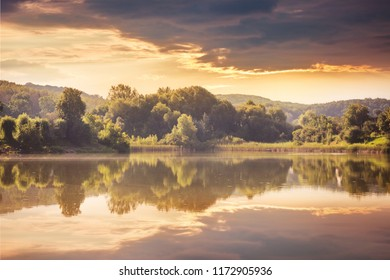 River and forest at sunset. Display trees and clouds in the water of the lake. Landscape with a river and trees in the evening