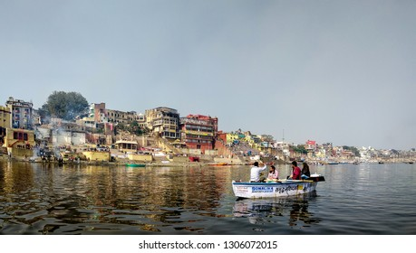 River Ganges, Varanasi, Uttar Pradesh, India; 30-Jan-2019; a panoramic view of a tourist boat with tourists with the Ganges riverfront in the background