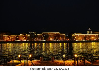 River and  glowing houses at night. Night scene.The Moscow river embankment. View to reflecting in water lights from buildings at embankment from another side of the river, Moscow, Russia