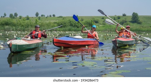 River Goryn. Ukraine. June 10, 2020; A group of tourists swim on the river in multi-colored kayaks.