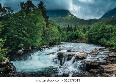 River high in the mountains in Norway, with flowing fresh light green water.