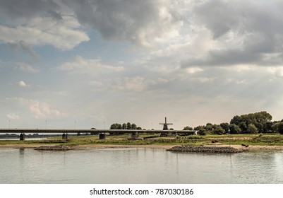 River IJssel with bridge and windmill under cloudy sky. Overijssel, Netherlands.