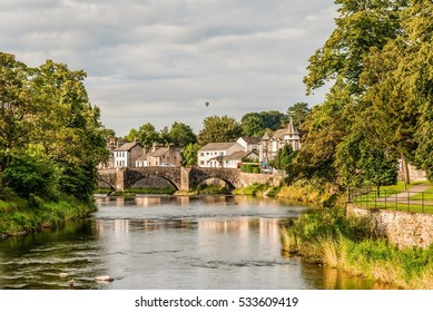 The River Kent, Kendal, Cumbria, England, with Nether bridge and a hot air balloon in the background
