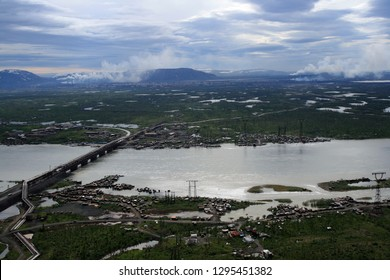 The river, lakes and tundra near Norilsk metallurgical plant. The bridge over the river and boat station in Norilsk on the Taimyr Peninsula. Ecology, pollution, smoke, nature protection