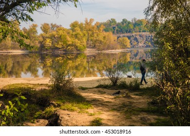 River landscape in autumn, two banks, a person walks on the river