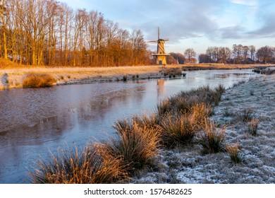 River landscape with a corn mill in winter season.