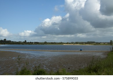 River landscape with floodplain in dutch canal with blue sky and big clouds. Sandbank with oil barrel in water and bushes all around. Image by Sonja Riedijk.