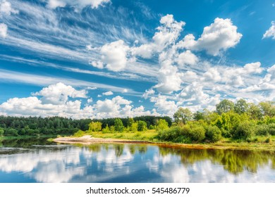 River Landscape With Reflections Of Clouds And Woods In Water. Summer. Sunny Day. Nobody. Natural Island