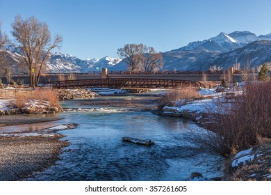 River leading to distant mountains and bridge in Ridgway, Colorado