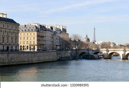 The river and left bank of thd Seine in Paris, on a sunny winter morning,  with the Pont Neuf, the oldest  bridge in Paris,  behind and the Eiffel Tower and Institut de France.