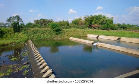 River management, a weir shaping river flow, with tetrapods below.Beside the weir, there are trees and green grass around photo Wide-angle shots in the middle of daylight use to background picture. - Shutterstock ID 1585299034