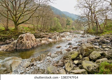The River Mawddach flows over and round white weathered rocks on a misty April day in the Welsh countrysdie.
