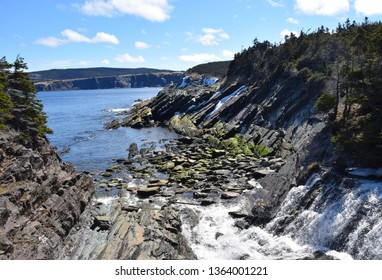 river meets ocean along a rocky shoreline  with heavy water flow in a forest area, Motion river, Torbay Newfoundland Canada
