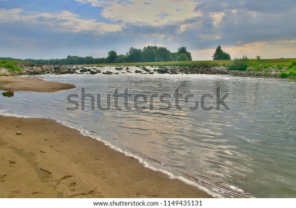 River Morava with sandy banks with vegetation and a stone and steel barrier, in front of a bridge connecting both shores of the state