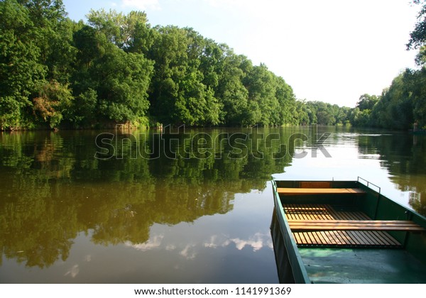 River Morava in a tranquil stream with banks lined by trees and a small tourist dock