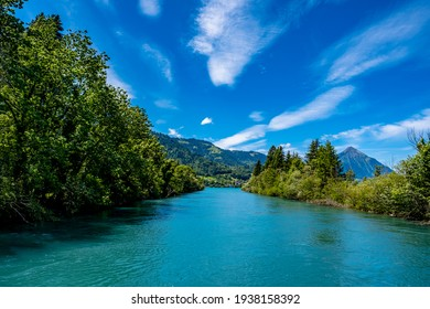 River and mountains with blue sky - Interlaken, Switzerland - Shutterstock ID 1938158392