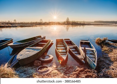 River and old rowing fishing boats at beautiful sunrise sunset in autumn morning