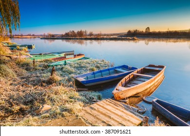 River and old wooden rowing fishing boat at beautiful sunrise in autumn morning.